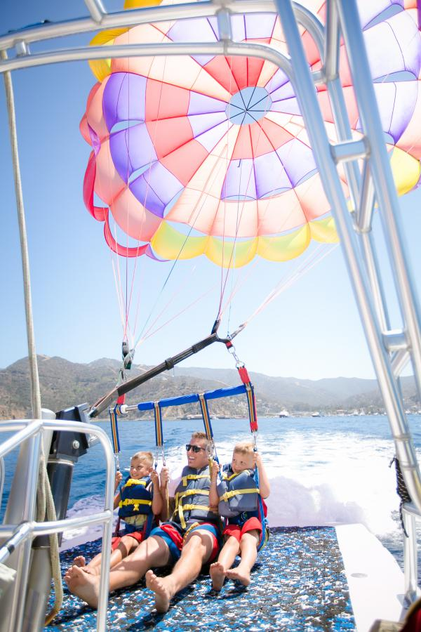 dad and two young boys about to take off on a parasail