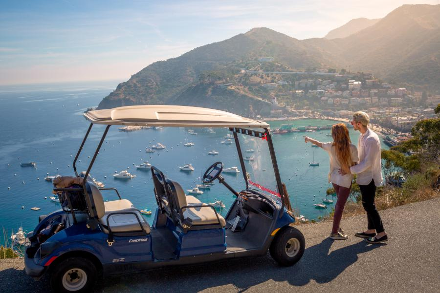 couple on golf cart tour enjoying the view of the harbor