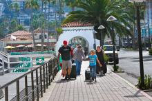 A family walking to their hotel after arriving in Avalon