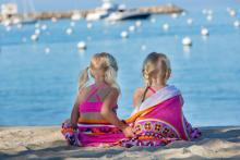 two young girls sitting on a beach